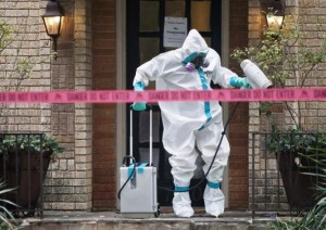 A member of the CG Environmental HazMat team disinfects the entrance to the residence of a health worker at the Texas Health Presbyterian Hospital who has contracted Ebola in Dallas